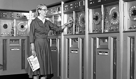 A vintage photograph of Grace Murray Hopper working with a large computer.