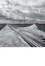 """Cover of the book titled """"Eye on the West,"""" depicting a deserted road intersecting with railroad tracks under a cloudy sky."""