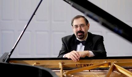 A man sitting at a grand piano.