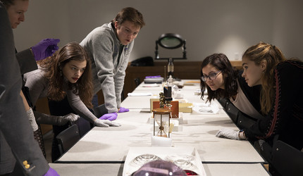 """The students of  """"Glass in America"""" examine objects from Yale's collections last fal"""