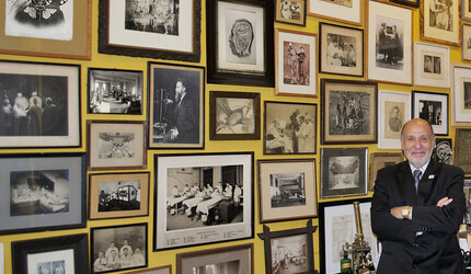 Stanley B. Burns stands with many of the photos at his New York City townhouse.