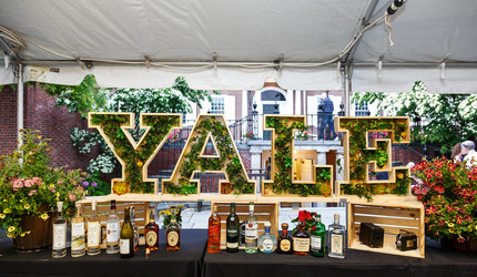 A floral display shaped like the Yale logo with liquor bottles underneath, at Yale reunion weekend.