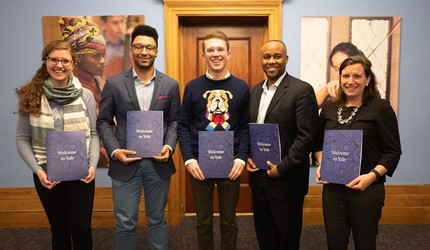 Yale admissions workers posing with welcome packets for Early Application admittees to the Class of 2023