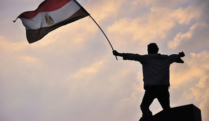 One of the protestors waving the Egyptian Flag during the protests in Tahrir Square, Cairo.