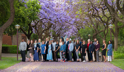 Conference participants pose amid Jacaranda trees, iconic for Pretoria which is known as the Jacaranda City.
