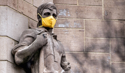 Statue on building wearing a face mask.