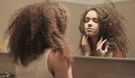 A teen girl looking at her skin in the mirror