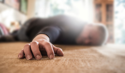 A person lying on the ground of their home