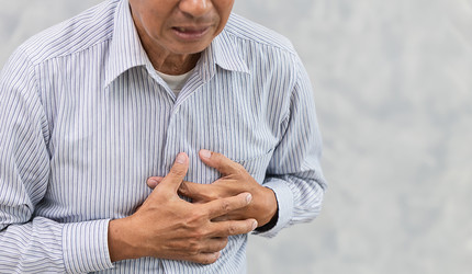 An elder Chinese man clutching his chest in pain.