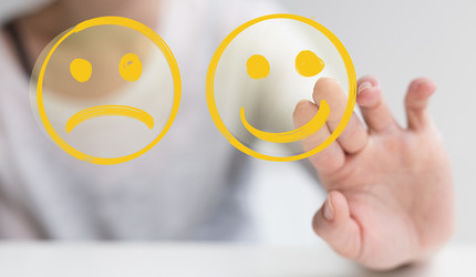 Hand is selecting a happy mood smiley. In front of an empty room.