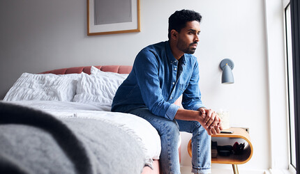 Depressed man sitting on his bed.