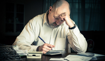 A distressed middle-aged man looking at a pile of bills.