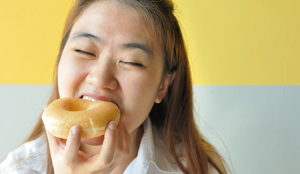 A woman biting into a glazed donut.