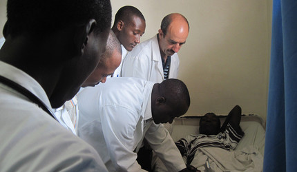 Dr. Andre Sofair, a professor of medicine at Yale, observing a Rwandan resident examining a patient.
