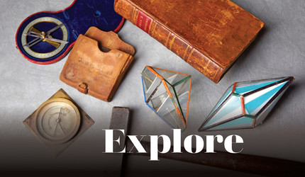 "An antique book, compass, and other vintage objects arranged on a table with the title ""Explore"""