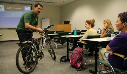 Douglas Noble demonstrating the mechanics of a bike during a bicycle safety course at Yale.