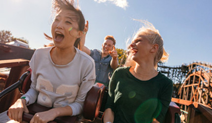 A male and two female teenagers on a rollercoaster ride.