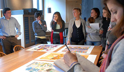 A teacher and students looking at artworks on a table.