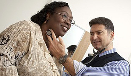 A white male doctor using a stethoscope to examine a black female patient.