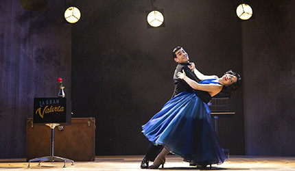 A actor and actress in formal attire dance on a stage.