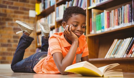 A young boy smiling and reading a book on the floor.