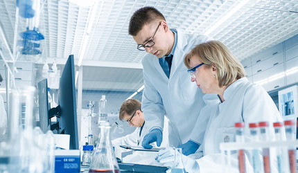In Modern Laboratory Senior Female Scientist Has Discussion with Young Male Laboratory Assistant.