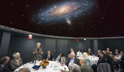 Conference participants listen to the honored speaker in a room with a galaxy projected on the ceiling.