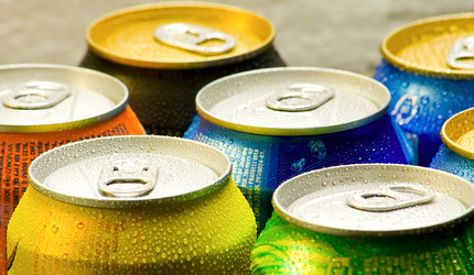 A photo of different soft drink cans, beaded with moisture, looking thirst-quenching as all get out.