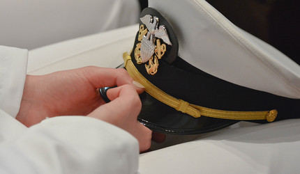 A Yale NROTC officer holds hat in hands.