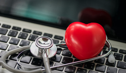 A stethoscope and toy heart on top of a laptop keyboard.