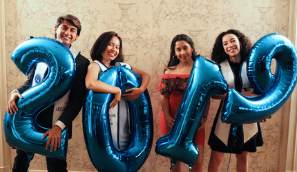 Latinx graduates posing with inflatable 2019 balloons