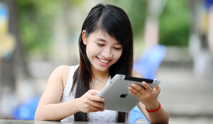 A young woman who is smiling and looking at her iPad while seated outside.