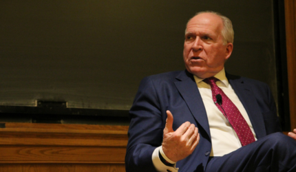 Former CIA director John Brennan delivering a lecture in a navy blue suit and red tie.