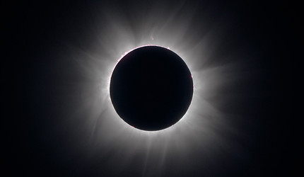 The sun's corona shines behind the moon