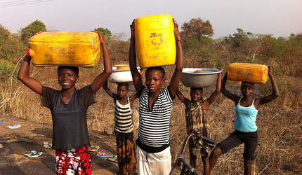 Female farmers carrying jugs of water in Africa.