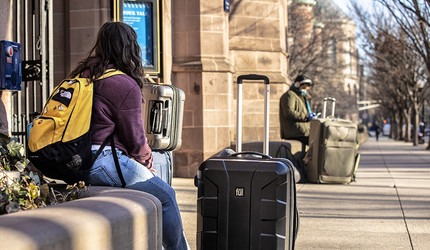 A Yale College student sits outside Pehlps Gate with her luggage as she waits for an airport shuttle to take her home