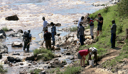 Scientists with nets and other equipment on the shore of the Mara river in Kenya.