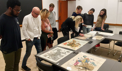 Students and professor with picturesque maps spread across the table.