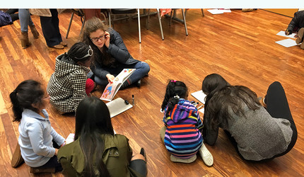 Yale students and schoolchildren on the floor, writing
