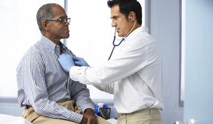 A white doctor with an African-American patient.