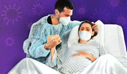 A woman in labor with the father, both wearing face masks.