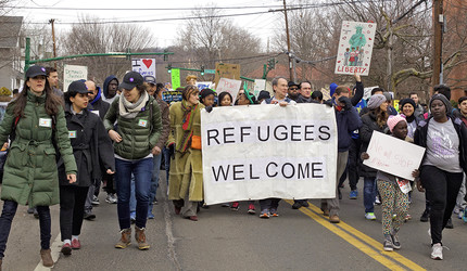 Activists carrying a Refugees Welcome banner during a protest march in New Haven, CT.