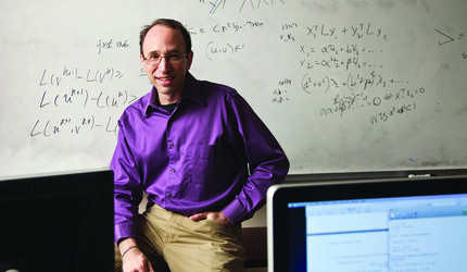 Daniel Spielman posing in front of a whiteboard covered in computations.
