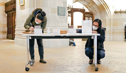 Students writing postcards in Sterling Memorial Library.