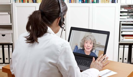 A doctor consults with a patient via teleconference on a laptop.
