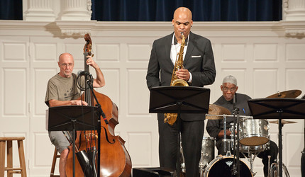 Saxophonist Wayne Escoffery performing with a drummer and bass player.