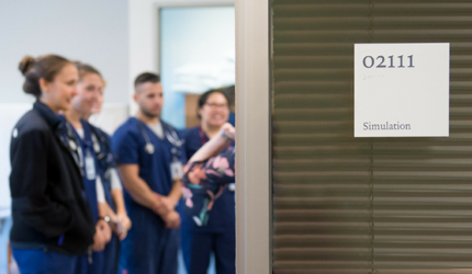 A room placard that says Simulation, with a group of nursing students in the background.