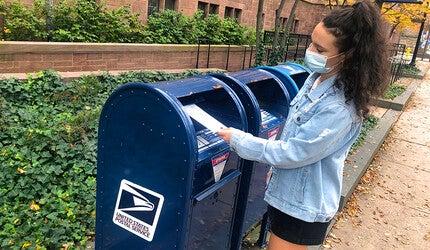 Student mailing an absentee ballot