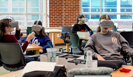 Teens wearing VR headsets.