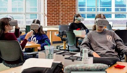 Teens wearing VR headsets.